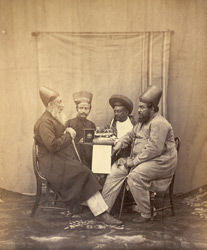 Studio portrait of three Parsees and a Parbhu, Bombay.